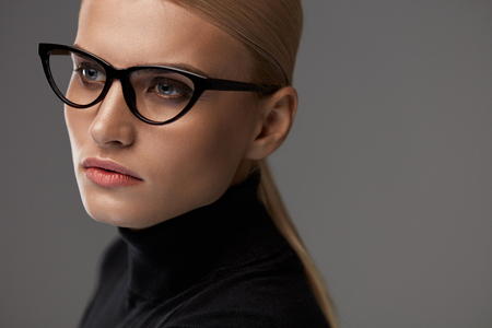 Women Eyewear. Beautiful Sexy Young Woman With Natural Face Makeup In Fashionable Stylish Optical Eye Glasses On Grey Background. Attractive Girl Wearing Black Fashion Glasses Frame. High Resolution