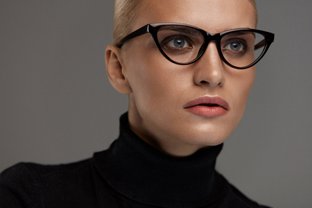 Foto de Female Eyeglasses. Portrait Of Beautiful Young Woman Wearing Black Eye Cat Design Glasses Frame, Fashion Eyewear. Attractive Blonde Girl In Stylish Optical Glasses On Grey Background. High Resolution - Imagen libre de derechos