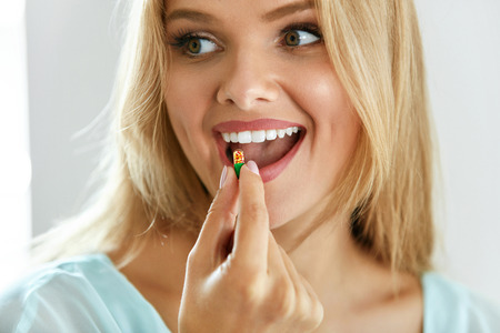 Woman Taking Medication Pill. Beautiful Smiling Girl Taking Medicine. Portrait Of Healthy Happy Female Holding Capsule In Hand. Vitamins And Food Supplements, Diet Nutrition Concept. High Resolution