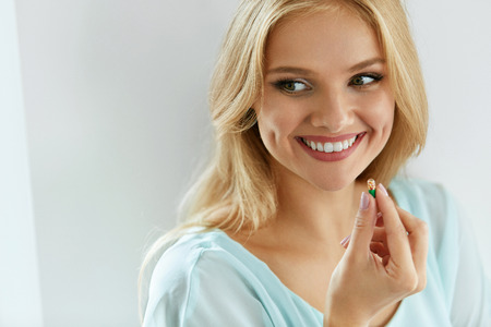 Photo pour Vitamins And Dietary Supplements. Portrait Of Beautiful Smiling Woman Holding Colorful Vitamin Pill In Hand. Closeup Of Happy Girl Taking Medication. Healthy Diet Nutrition Concept. High Resolution - image libre de droit