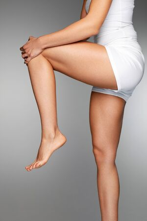Photo pour Woman Body Part. Closeup Of Beautiful Female Hands Holding Her Long Slender Leg. Close-up Of Girl Stretching Legs, Touching Painful Knee And Feeling Pain In Knee. Health Care Concept. High Resolution - image libre de droit