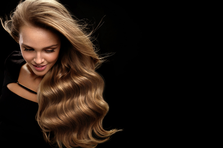 Foto de Beautiful Long Hair. Fashion Female Model With Beauty Face Makeup And Healthy Shiny Blonde Wavy Curly Hair On Black Background. Portrait Of Woman With Gorgeous Hairstyle And Hair Color. High Quality - Imagen libre de derechos