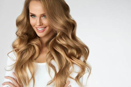 Photo for Beautiful Curly Hair. Smiling Girl With Healthy Wavy Long Blonde Hair. Portrait Happy Woman With Beauty Face, Sexy Makeup And Perfect Hair Curls. Volume, Hairstyle, Hairdressing Concept. High Quality - Royalty Free Image