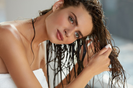 Foto de Hair And Body Care. Portrait Of Beautiful Young Female Model After Bath Applying Hair Oil. Closeup Of Sexy Woman In Towel Drying Wet Long Hair. Health And Beauty Concept. High Resolution Image - Imagen libre de derechos