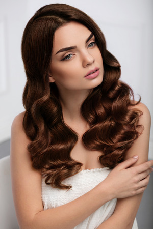Foto de Curly Hair Style. Beautiful Brunette Woman Model With Long Shiny Wavy Hairstyle. Gorgeous Girl With Natural Makeup, Beauty Face, Healthy Soft Skin, Perfect Brown Hair Color And Curls. High Resolution - Imagen libre de derechos