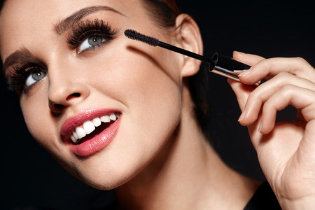 Foto de Beauty Makeup And Cosmetics. Closeup Of Beautiful Woman Face With Soft Skin, Perfect Professional Facial Make-up Applying   Black Mascara On Long Thick Eyelashes With Cosmetic Brush. High Resolution - Imagen libre de derechos