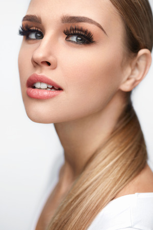 Photo pour Beauty Woman Face. Closeup Of Beautiful Young Female Model With Soft Smooth Skin And Professional Facial Makeup. Portrait Of Sexy Girl With Long Fake Eyelashes And Perfect Make-up. High Resolution - image libre de droit
