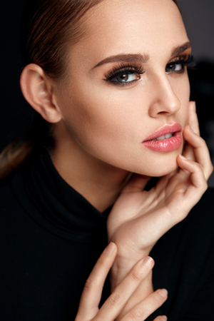 Photo pour Beauty Woman Portrait. Beautiful Fashionable Woman With Perfect Facial Makeup, Soft Pure Clean Face Skin And Long Black Thick Fake Eyelashes On Black Background. Cosmetics Concept. High Resolution - image libre de droit