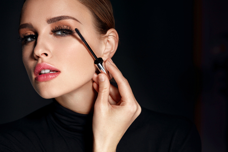 Beauty Cosmetics. Closeup Of Beautiful Sexy Woman Putting Black Mascara On Long Thick Eyelashes With Brush. Fashionable Female Model With Soft Skin, Perfect Makeup And Fake Eyelashes. High Resolutionの写真素材