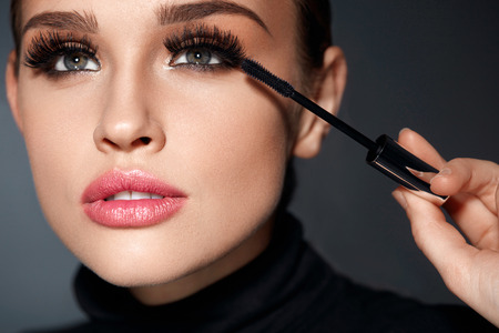 Foto de Beauty Make-up. Portrait Of Beautiful Young Woman With Fake Eyelashes Applying Black Mascara On Lashes, Holding Brush In Hand. Sexy Female With Soft Skin And Perfect Makeup. Cosmetics. High Resolution - Imagen libre de derechos