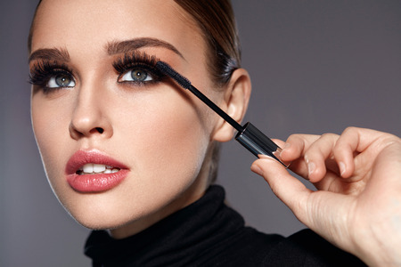 Beauty Make-up. Portrait Of Beautiful Young Woman With Fake Eyelashes Applying Black Mascara On Lashes, Holding Brush In Hand. Sexy Female With Soft Skin And Perfect Makeup. Cosmetics. High Resolutionの写真素材