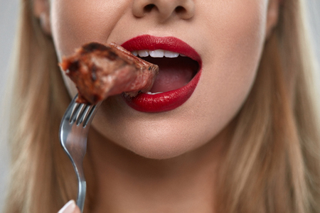 Foto für Eating Meat. Closeup Of Woman Mouth With Red Lips, White Teeth Biting Tasty Beef Steak On Fork. Close-up Of Beautiful Female Mouth Eating Delicious Grilled Meat. Nutrition Concept. High Resolution - Lizenzfreies Bild