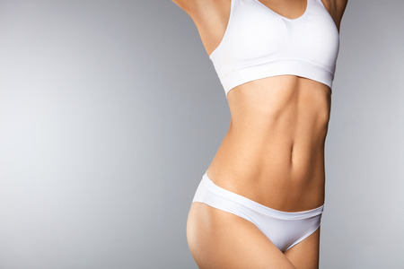 Foto de Body Care. Beautiful Woman In Shape With Fit Slim Body, Healthy Smooth Soft Skin In White Bikini Panties On Gray Background. Closeup Female Body In Underwear. Health And Diet Concepts. High Resolution - Imagen libre de derechos