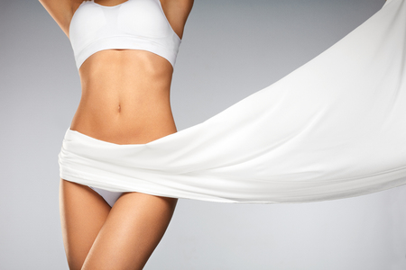 Foto de Women Health. Beautiful Healthy Woman With Fit Slim Body, Silky Smooth Soft Skin In White Bikini Underwear. Closeup Of Textile Flying On Perfect Female Body Shape. Body Care Concept. High Resolution - Imagen libre de derechos