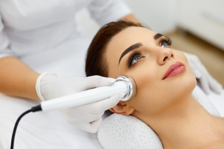 Photo pour Cosmetology. Beautiful Woman Receiving Facial Skin Ultrasound Cavitation. Closeup Of Female Face Receiving Anti-Aging Cosmetics Using Ultrasound Cavitation Machine. Body Care. High Resolution - image libre de droit