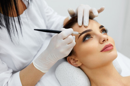 Foto de Permanent Makeup For Eyebrows. Closeup Of Beautiful Woman With Thick Brows In Beauty Salon. Beautician Doing Eyebrow Tattooing For Female Face. Beauty Procedure. High Resolution - Imagen libre de derechos