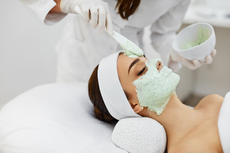 Photo pour Facial Skin Treatment. ?loseup Of Beautiful Young Woman Receiving Cosmetic Mask In Beauty Salon. Beautician Applying Alginate Mask On Female Face With Smooth Soft Skin. Cosmetology. High Resolution - image libre de droit