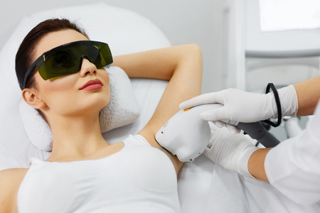 Laser Hair Removal. Closeup Of Beautician Removing Hair Of Young Woman's Armpit. Beauty Epilation Treatment In Cosmetic Beauty Clinic. Hairless Smooth And Soft Skin. Body Care. High Resolution