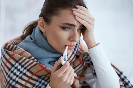 Photo pour Health Care. Closeup Of Beautiful Ill Woman With Headache, Sore Throat And Fever Covered In Blanket Feeling Sick, Measuring Body Temperature With Thermometer. Sickness And Illness. High Resolution - image libre de droit