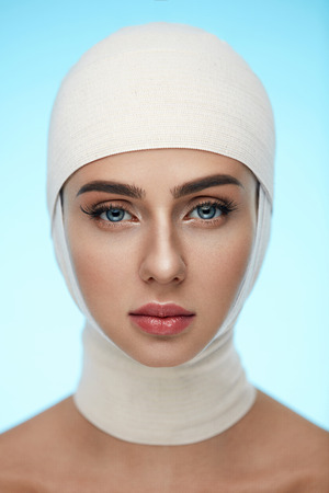Plastic Surgery. Portrait Of Beautiful Young Woman With Head Wrapped In Medical Bandages. Closeup Of Healthy Woman Face With Smooth Soft Skin And Perfect Makeup. Cosmetic Treatment. High Resolution
