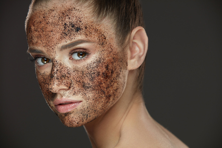 Face Care. Closeup Of Young Woman With Natural Makeup And Coffee Scrub Mask On Fresh Facial Skin. Portrait Of Beautiful Sexy Female Model With Peeling Cosmetic Product On Beauty Face. High Resolution