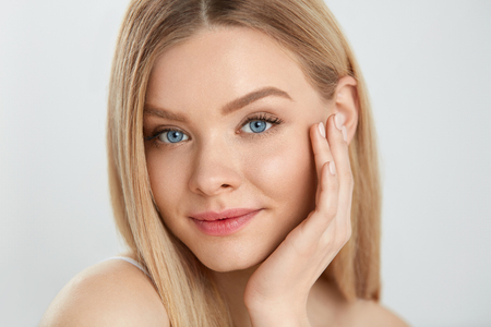 Woman Beauty Face Skin. Closeup Of Beautiful Young Female Model With Healthy Soft Smooth Skin And Fresh Natural Makeup. Portrait Of Attractive Smiling Girl Touching Face. Facial Care. High Resolution