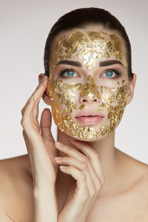 Photo pour Woman Face Beauty. Portrait Of Beautiful Female Holding Hands Near Head And Golden Mask On Face Skin. Closeup Sexy Girl With Natural Makeup And Skin Cosmetics Product On Facial Skin. High Resolution - image libre de droit