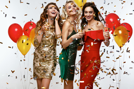 Foto de Beautiful Women Celebrating New Year, Having Fun At Party. Portrait Of Happy Smiling Girls In Stylish Glamorous Dresses With Champagne Glasses At Fashion Party. High Resolution. - Imagen libre de derechos