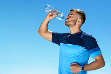 Foto de Man Drinking Water After Running. Portrait Of Handsome Athletic Male In Colorful Sportswear Resting After Fitness Workout, Drink Water From Bottle On Blue Sky Background. - Imagen libre de derechos
