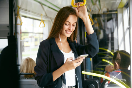 Foto de Woman Listening Music On Phone Riding In Bus. Portrait Of Stylish Smiling Girl Listening Music In Headphones, Using Smartphone While Riding In Public Transport. High Resolution. - Imagen libre de derechos