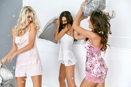 Foto de Pillow Fight. Sexy Women Having Fun At Home Party. Beautiful Smiling Female Models In Stylish Sexy Pajamas Playing And Fighting WIth Pillows At Pajama Party. High Resolution - Imagen libre de derechos