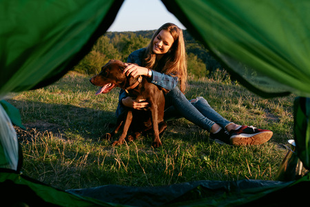 Photo pour Beautiful Smiling Girl Playing With Pet, Sitting Near Tent On Grass And Enjoying Summer. Travel Concept. High Quality Image. - image libre de droit