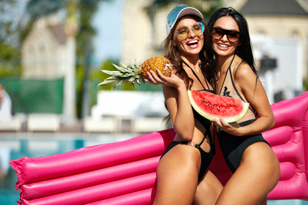 Summer Fashion. Girls In Swimsuits Having Fun Near Pool On Vacation. Sexy Female Models In Trendy Sunglasses And Fashionable Swimwear With Tanned Bodies, Air Mattress And Fruits. High Quality Image.