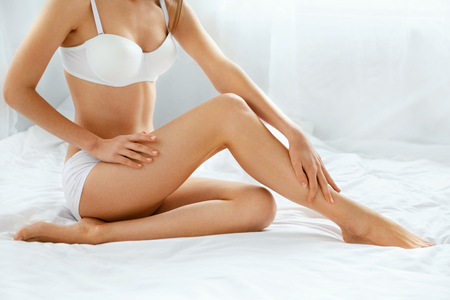 Foto de Beautiful Female With Long Legs And Smooth Skin. Close Up Of Woman Body With Soft Depilated Long Legs With Perfect Smooth Soft Skin And Beautiful Hands. Hair Removal, Skin Care Concept. High Quality - Imagen libre de derechos