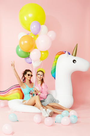 Foto de Summer Fashion Girls Having Fun With Balloons On Unicorn Float. Beautiful Smiling Women In Fashionable Clothes And Swimwear With Colorful Balloons On Pink Background. Women Style. High Quality Image. - Imagen libre de derechos