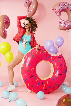 Summer Fashion. Woman In Swimsuit With Balloons. Beautiful Happy Young Female Model With Fit Body In Fashionable Colorful Swimwear With Inflatable Donut Floats On Pink Bakcground. High Resolution.