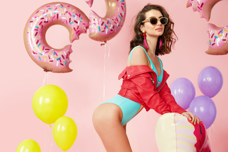 Foto de Woman In Summer. Fashion Model in Swimsuit And Sunglasses. Beautiful Smiling Female With Sexy Body In Fashionable Sunglasses, Trendy Swimwear Having Fun With Floats And Balloons Indoors. High Quality - Imagen libre de derechos