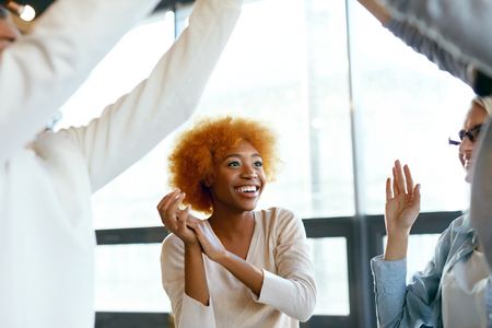 Happy Woman Having Fun In Office. Portrait Of Beautiful Smiling Young African Female Laughing, Clapping Hands, Dancing And Celebrating At Work. High Quality Image