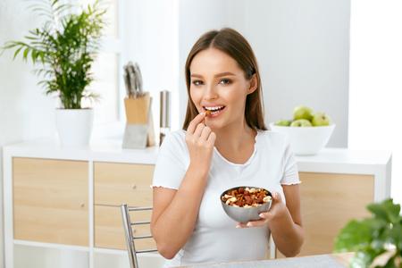 Foto de Healthy Nutrition. Beautiful Young Woman Eating Nuts - Imagen libre de derechos