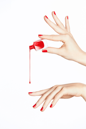 Photo pour Red Nail Polish. Hand With Red Nails On White Background. Close Up Of Female Hands With Smooth Soft Skin And Bright Color Manicure Pouring Nail Polish From Bottle. High Quality Image. - image libre de droit