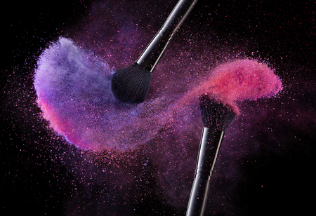 Photo for Cosmetic Brushes And Explosion Colorful Powders. Close Up Of Makeup Soft Blush Brushes Releasing Cloud Of Violet And Pink Powder Splash On Black Background. Makeup Tools. High Quality Image. - Royalty Free Image