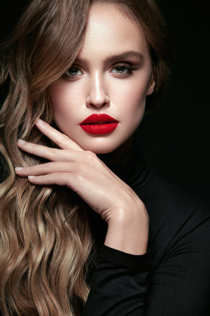 Photo pour Beautiful Woman With Beauty Makeup And Hairstyle. Portrait Of Young Female Model With Sexy Glamorous Face, Red Lips And Long Wavy Hair On Black Background. Cosmetics Concept. High Resolution. - image libre de droit