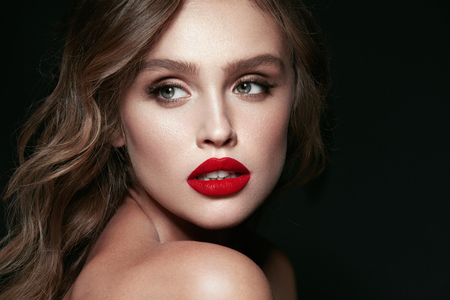 Beauty Face. Beautiful Woman With Makeup And Red Lips. Portrait Of  Young Sexy Female Model With Stylish Hairstyle, Perfect Smooth Soft Skin And Red Lipstick On Sexy Full Lips. High Resolution.