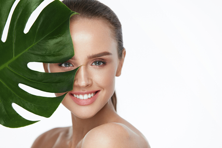 Photo pour Facial Beauty. Beautiful Woman With Fresh Healthy Skin Holding Green Plant On White Background. High Resolution. - image libre de droit