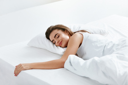 Photo pour Healthy Sleep. Woman Sleeping On White Bedding, WIth Soft Pillow, Mattress With Blanket. High Resolution. - image libre de droit