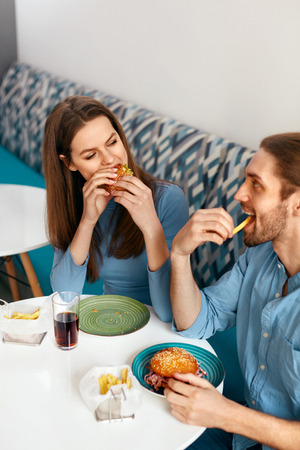 Friends Eating Burgers Indoors. Smiling People Eating Hamburgers In Fast Food Cafe. High Resolution