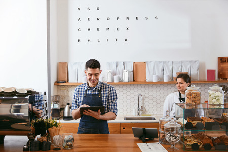 Photo pour Young Barista Working On Tablet In Cafe, Standing Near Workplace. High Resolution. - image libre de droit