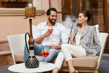 Photo for Couple Smoking Shisha With Fruit Cup In Hookah Bar. Man And Woman Smoke Hookah, Drinking Cocktails In Cafe. High Resolution - Royalty Free Image