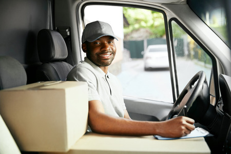 Photo pour Courier Delivery. Black Man Driver Driving Delivery Car - image libre de droit