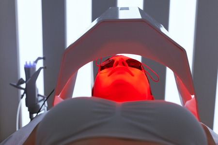 Foto de Cosmetology. Woman Face Getting Red Light Oxygen Treatment At Beauty Clinic. Facial Photo Therapy. High Resolution - Imagen libre de derechos
